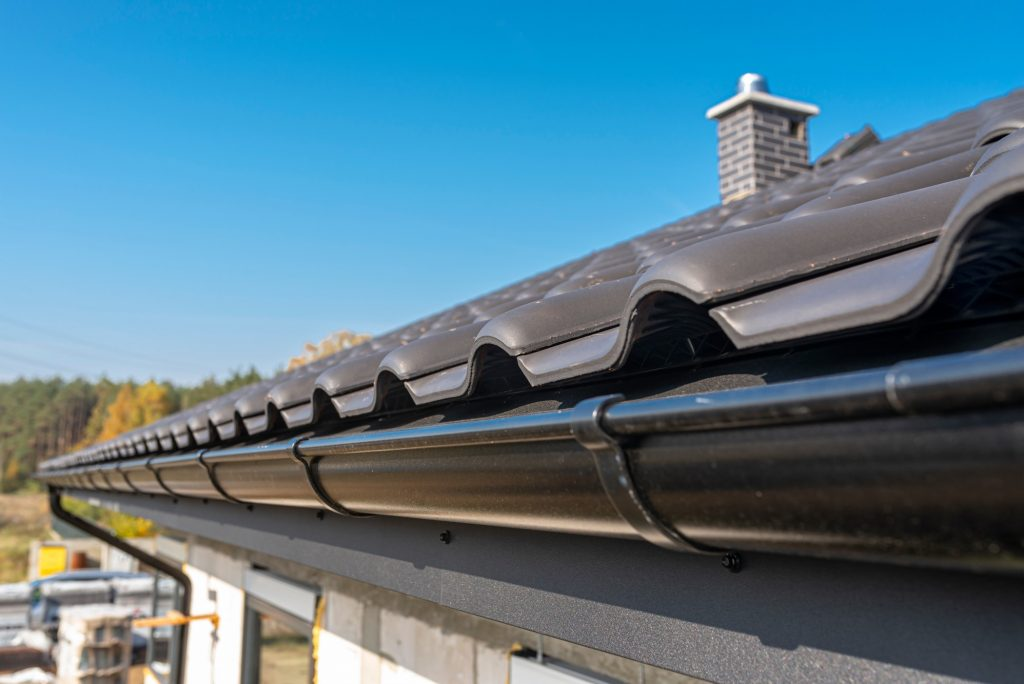a-metal-black-gutter-on-a-roof-covered-with-ceramic-tiles-close-up-shot-roof-gutter-gutter-roofing_t20_6m0E4O