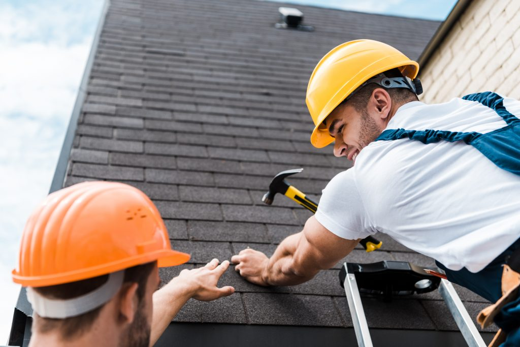 RainTech Roofing - low angle view of repairman looking at coworker while holding hammer